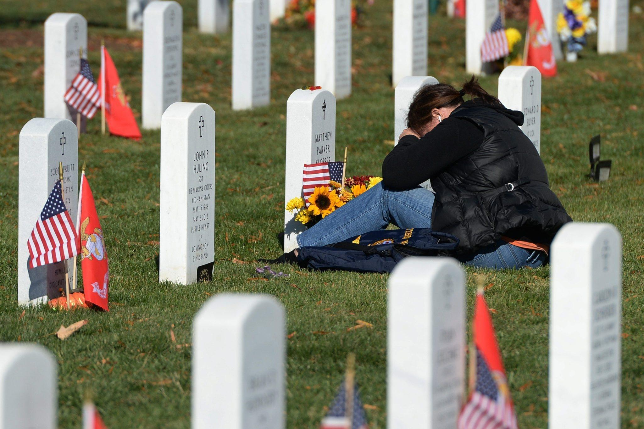 With 2,300 U.S. troop deaths over the dozen years of the war in Afghanistan, public dismay over the faraway battle now matches the height of U.S. opposition to the war in Iraq, an ABC News/Washington Post poll disclosed Friday. In this photo from Arlington National Cemetery on Veteran's Day last month, Kathy Sheehy weeps in front of the gravestone of her son, Lt. Matthew Klopfer, a naval aviator who died in June 2012.