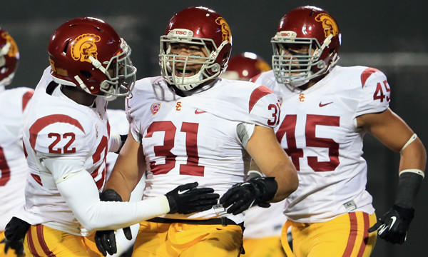USC's Soma Vainuku, center, is congratulated by teammate Leon McQuay III, left, after blocking a punt in a win over Colorado in November. The Trojans' trek to the Las Vegas Bowl hasn't been an easy one.
