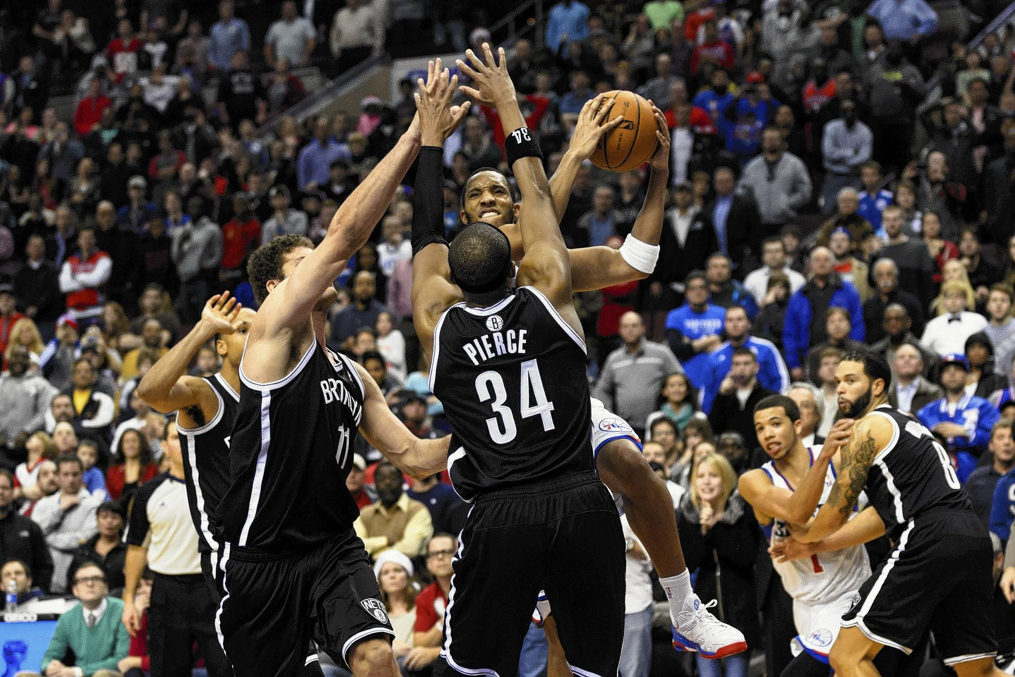 Dec 20, 2013; Philadelphia, PA, USA; Philadelphia 76ers guard Evan Turner (12) puts up the game winning shot in overtime as Brooklyn Nets center Brook Lopez (11) and forward Paul Pierce (34) defend at the Wells Fargo Center.