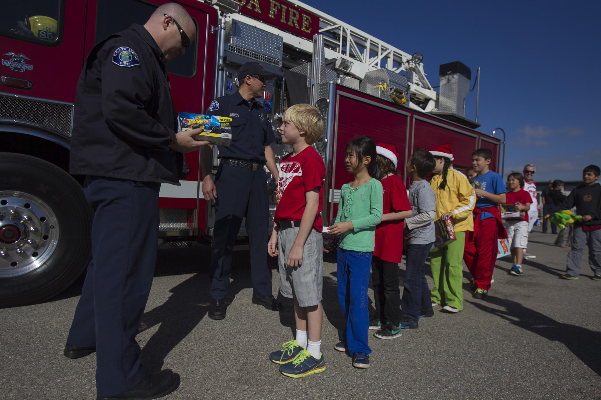 Costa Mesa Firefighter Ken McCart left, and Engineer Anthony Mancillas take a gift from Kaiser Elementary School student Breden Hayward, 8, for the Costa Mesa Fire Department's charity Spark of Love on Friday, December 20. (Scott Smeltzer, Daily Pilot)