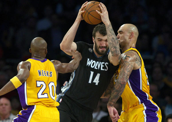 Lakers guard Jodie Meeks tries to help center Robert Sacre stop a driving by Timberwolves center Nikola Pekovic (14) in the first half Friday night at Staples Center.