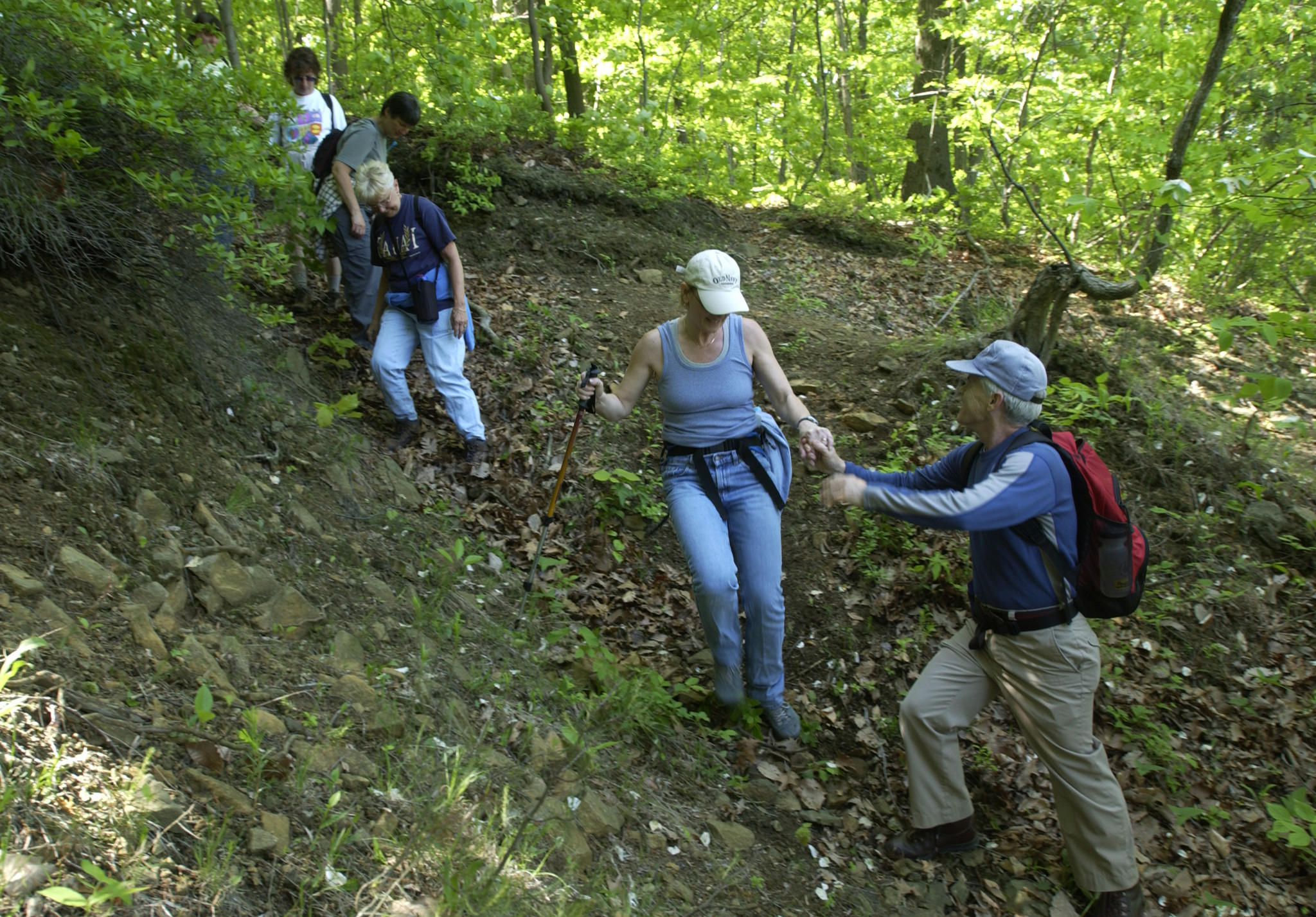 Baltimore, MD -- 5/14/03 -- Bill Bauer (right) assists Marry Moore down a steep section of trail in Leakin Park while hiking a nine-mile circuit with the Wednesday Walkers hiking club. Photo by Jerry Jackson/Staff
