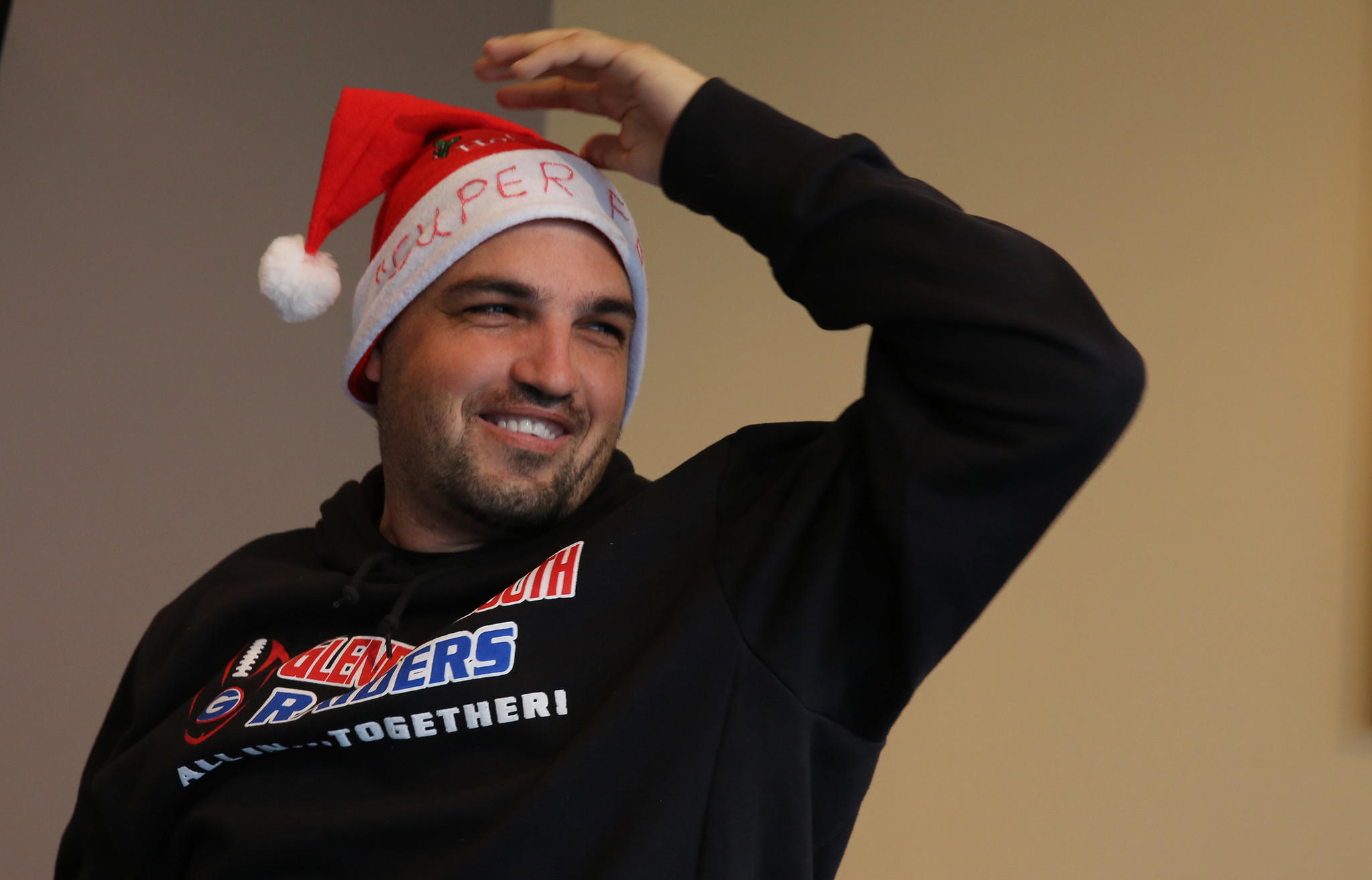 """Dave Key wears a Santa hat with the words """"super fan"""" and is all smiles after receiving new teeth for Christmas."""