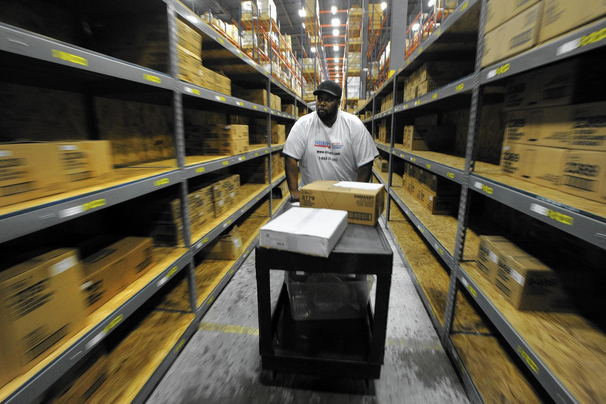 Dwayne Wesley a picker and packer at the warehouse fills an order as he walks through the warehouse. The recession and its long aftermath affected different parts of the state in wildly disparate ways, a Sun analysis shows.