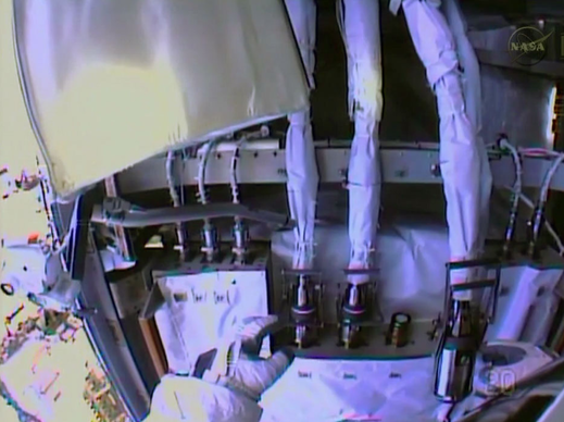 Spacewalker Rick Mastracchio works to disconnect the fluid lines from a malfunctioning ammonia pump module in this view from the NASA astronaut's helmet camera.