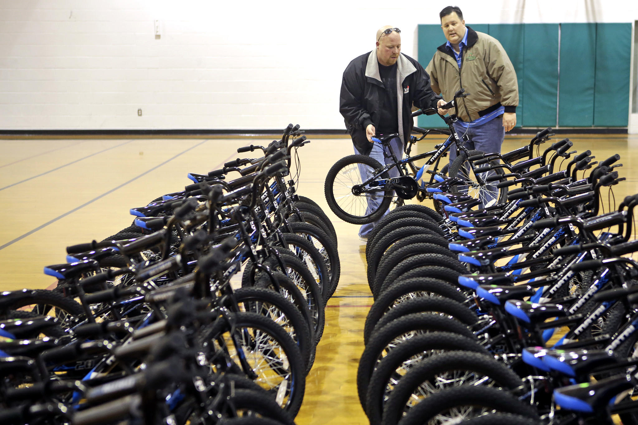 Douglas Atkins, left, and Jim Hicks, right, line up donated bicycles inside the YMCA gymnasium Saturday morning. The Rotary Club of Oyster Point assembled hundreds of bicycles and delivered them to the YMCA to be distributed to children.