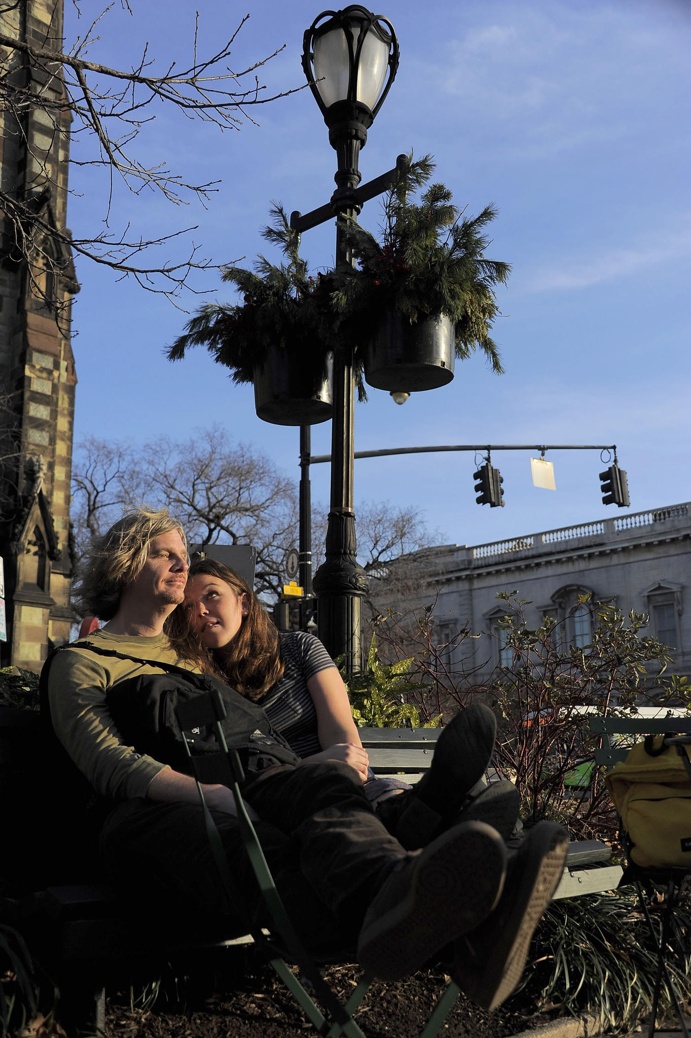 The only clues that this is the first day of winter are the lack of leaves on the trees and the installation of holiday evergreens above Joseph Young and Amanda McCormick of Baltimore, who enjoy the Winter Solstice with an unofficial temperature in the 70s at Mount Vernon Place.