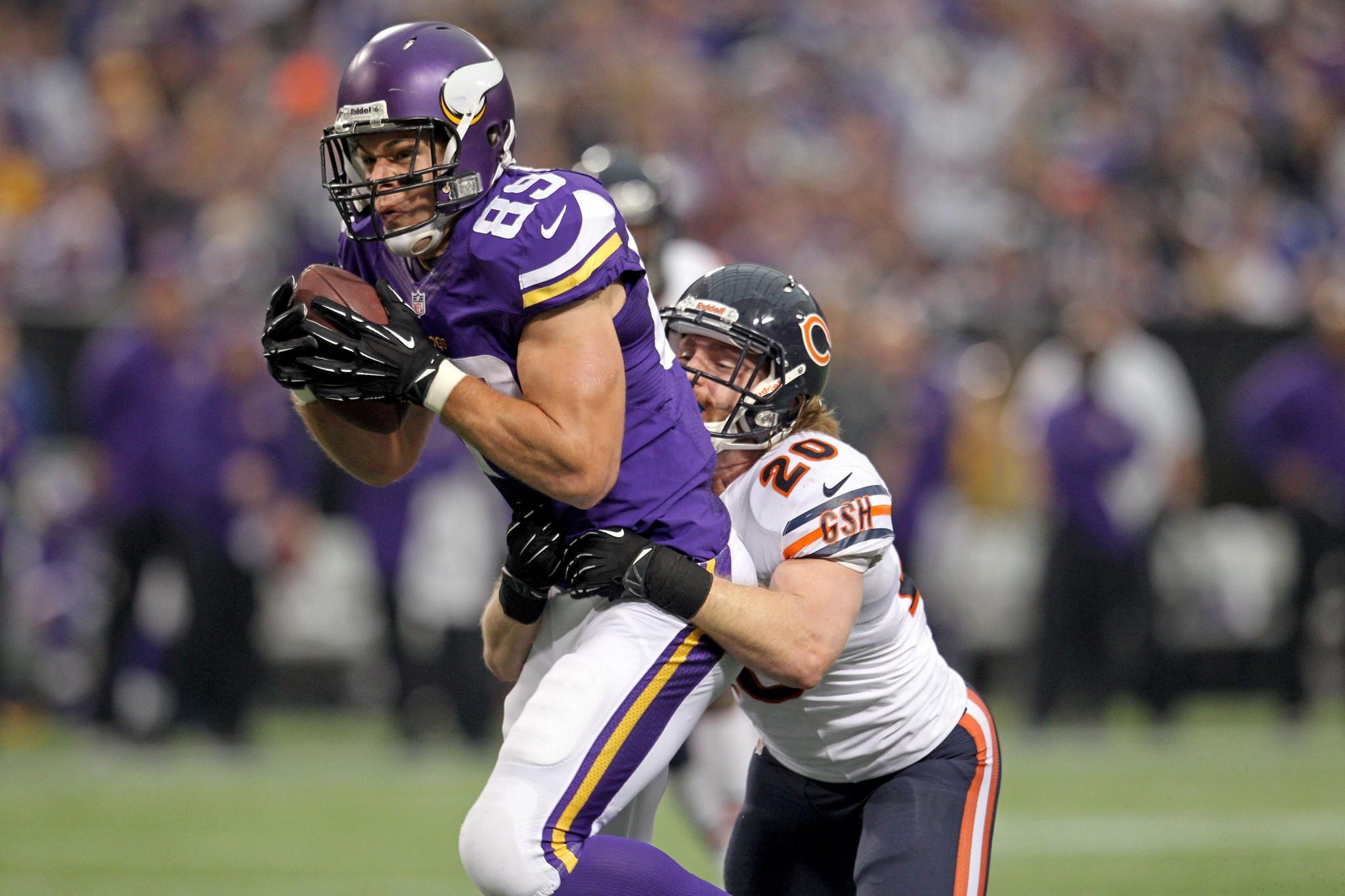 Vikings tight end John Carlson is tackled by Craig Steltz during the third quarter at Mall of America Field at H.H.H. Metrodome.