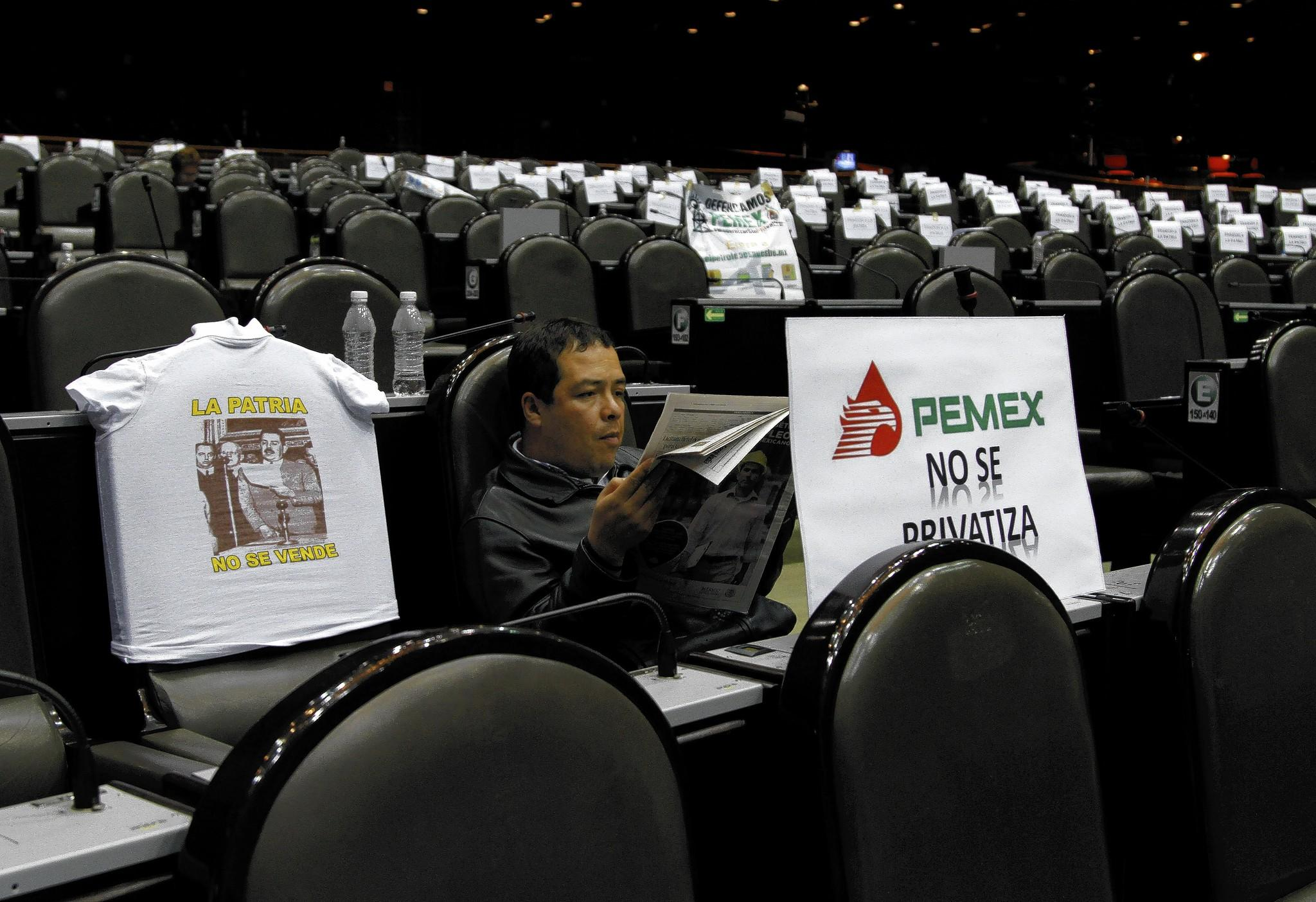 A lawmaker reads a newspaper this month, a day after leftists tried to block discussion of Mexico's energy reform bill. The legislation's advance is the latest blow to the Mexican political left.