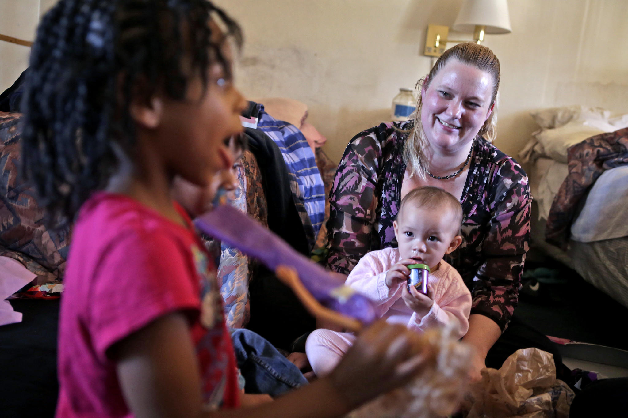Jammie Abbott, right, smiles as Zaleigh Dolberry, left, plays with gifts donated by Abbott Thursday afternoon. Zaleigh, her twin sister Zaniya and their mother Chanel Rivers are currently living in a motel in Hampton. Abbott is holding her one-year-old Ione Abbott.