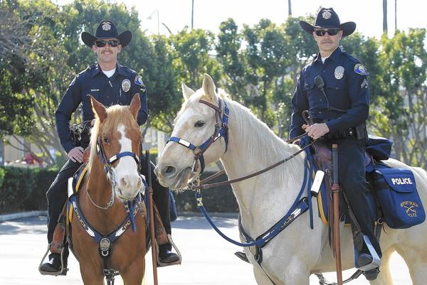 Officers Shawn Dugan, left, seated atop his horse Levi, and Matt Graham, right, seated atop his horse Pistol, pose for a portrait on Saturday. The Newport Beach Police Department hired mounted patrols for the first time to help keep watch at Fashion Island during the holiday season. (Kevin Chang/ Daily Pilot)