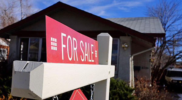 "A ""For Sale"" sign stands in the yard of a single family home in Denver, Colorado."