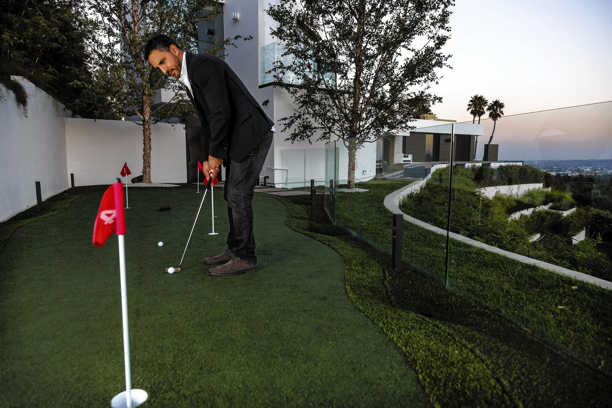 Real estate agent Mauricio Umansky tries out the putting green at a $36 million home for sale in Beverly Hills. The price includes a $300 putter.