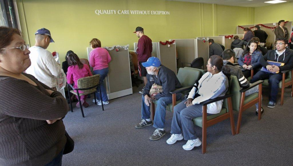 People wait to sign up for health insurance at an AltaMed enrollment center in east Los Angeles.