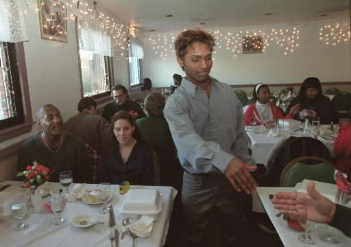 Raju Gomes,then age 17, of Manchester, walks to each table and thanks his guests for coming to dinner on Christmas Day at his father's South Windsor restaurant. Gomes, then a senior at Manchester High School, spent his own money to host the party for homeless people.