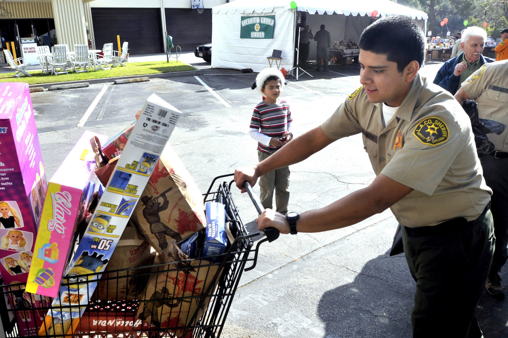 Explorer Richard Grandes pushes a cart filled with toys and food while helping a family of five at Crescenta Valley Sheriff's Station. Deputies, explorers and volunteers handed out Christmas gifts and bags of food to people in need on Saturday, Dec. 21, 2013.