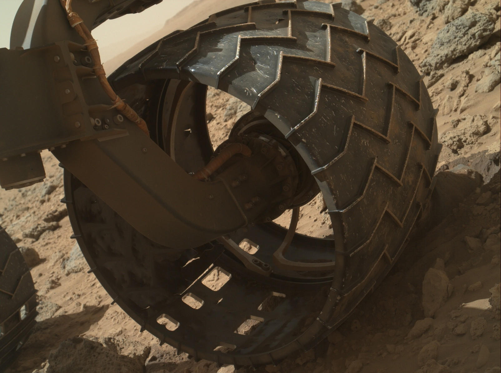 The left front wheel of NASA's Mars rover Curiosity shows dents and holes that could have been the result of sharp rocks on rough terrain, officials at the Jet Propulsion Laboratory say.
