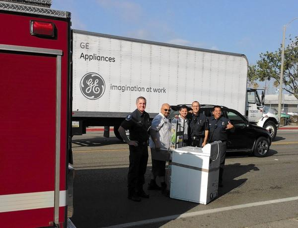 Costa Mesa firefighter paramedics Chuck Torres and Todd Palombo, Capt. Jason Pyle and engineer Eliasar Maldanado stand with a dryer they are donating to Heritage House South in Costa Mesa.