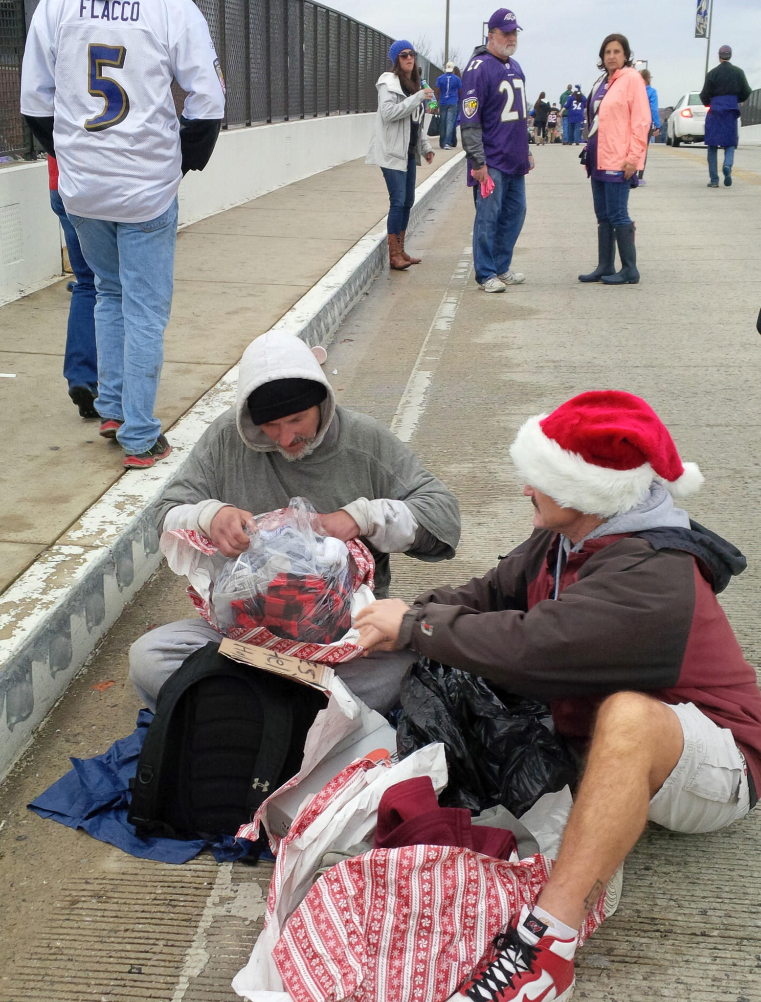 Jimmy Scaletta sits in the middle of the eastbound lane of the Hamburg Street Bridge with his cup and cardboard sign facing the incoming fans, hoping for handouts. On Sunday, Ravens fan Drew Haugh stopped by with a bag of gifts, celebrating Christmas with Scaletta on the morning of the Ravens-Patriots game.