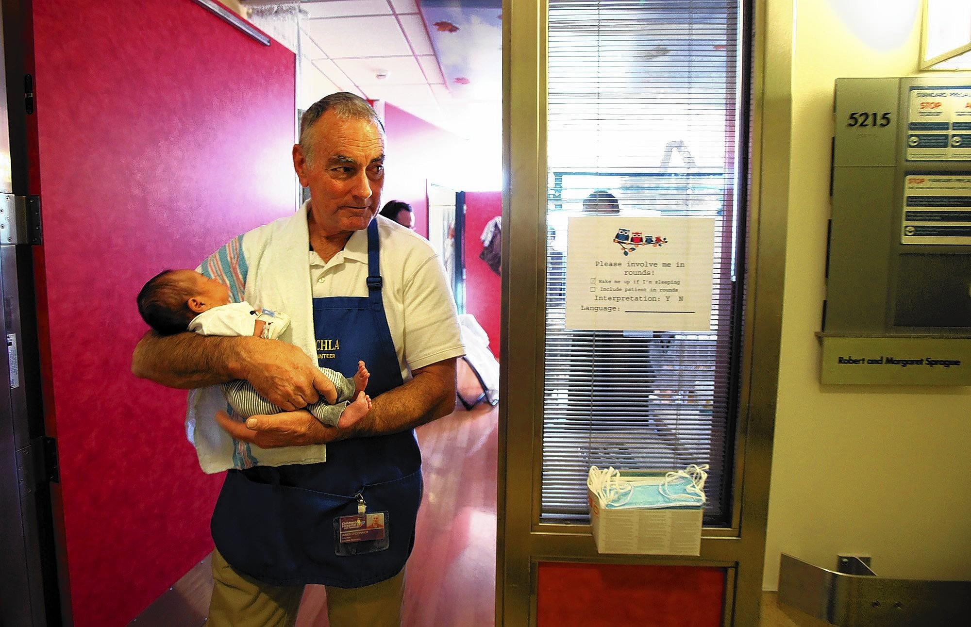 Jim O'Connor carries month-old patient Mace De Luna at Children's Hospital. O'Connor is known for his no-nonsense demeanor in the classroom, but he is a frequent blood donor and volunteers at Children's Hospital.