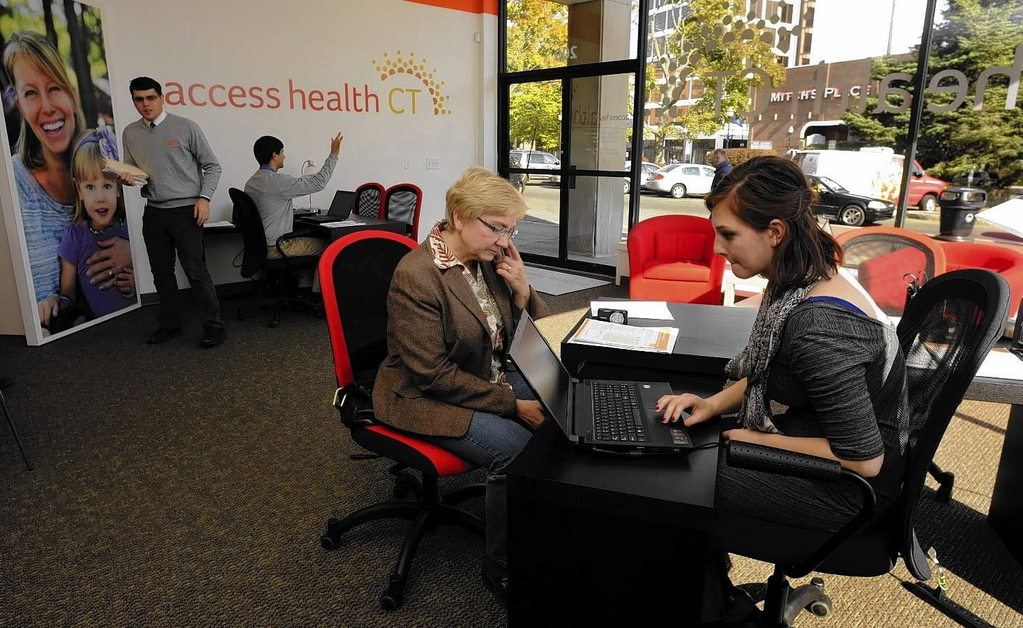 Monica Caballeros, of Hartford, (right) a bi-lingual outreach worker, answers questions for Stanislawa Rodriguez, of New Britain, about obtaining health insurance through Connecticut's new health exchange at Access Health CT's newly opened storefront in New Britain Tuesday. Rodriguez lost her job - and her health care - several years ago, and has been self-insured since. She is looking into puchasing health care for her family through the new exchange that was created through the Affordable Care Act.