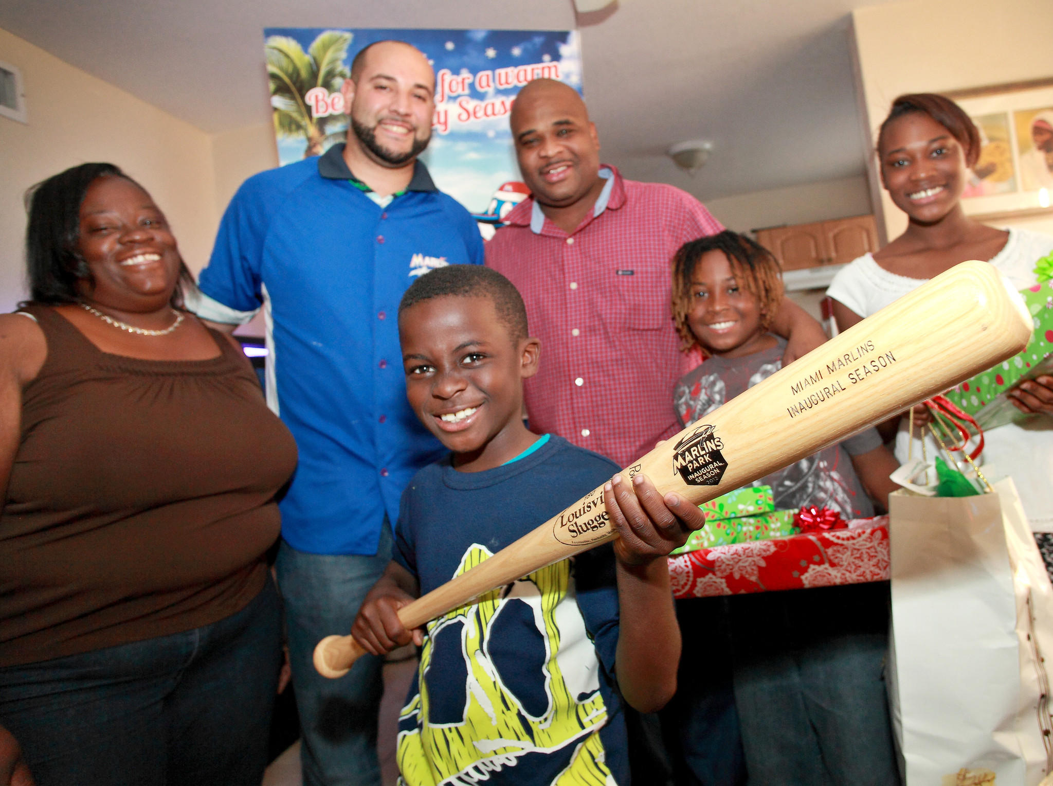 Juan Garciga, Marlins Community Outreach, center, poses next to (from left) Chrisie Clark, her son Quentin, 8, her husband James, her older son Amantay, 10, and her daughter Quantirel, 14, all members of the Clark family in Hollywood on December 20, 2013. The Marlins delivered Christmas gifts to the family.