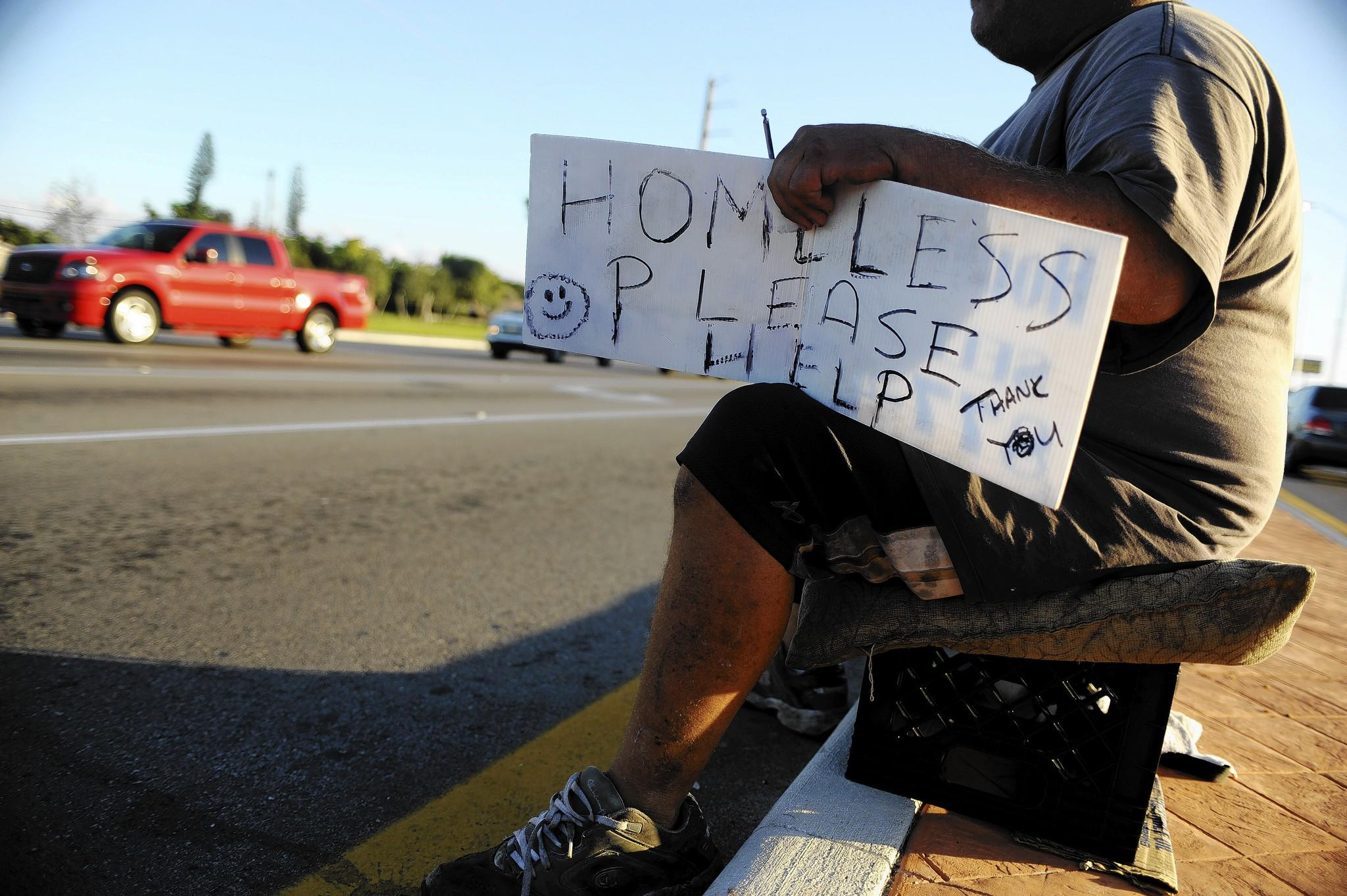 "File photo of a homeless man holds a sign that reads, ""Homeless Please Help, thank you"" on State Route 7 and Miramar Parkway in Miramar on December 3, 2010."