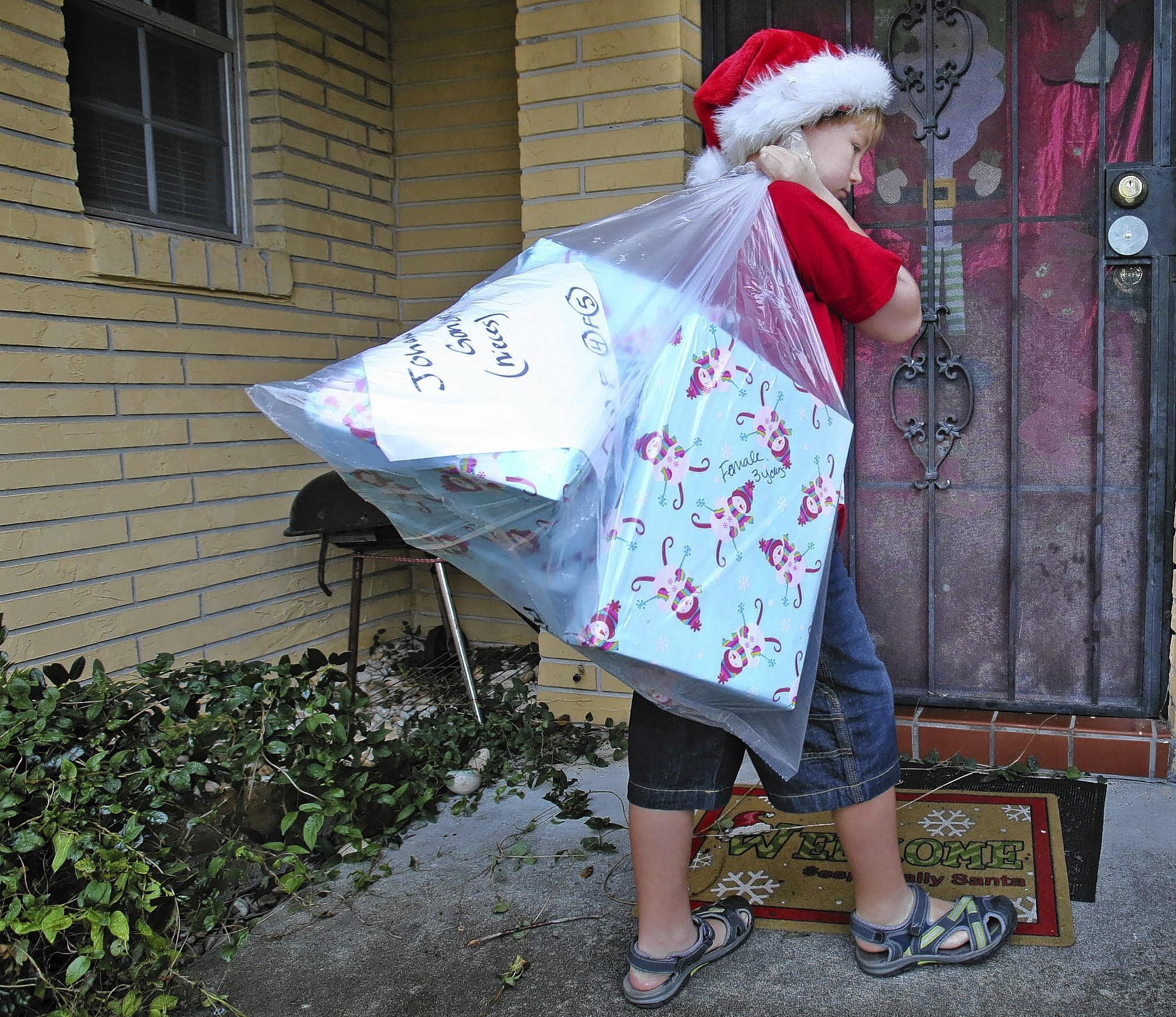 Gray Powell, 8, delivers a sack full of gifts Tuesday, December 24, 2013, to a family in Orlando. Gray and his father, Dudley Powell, worked as volunteers for One Heart for Women and Children, a local nonprofit.