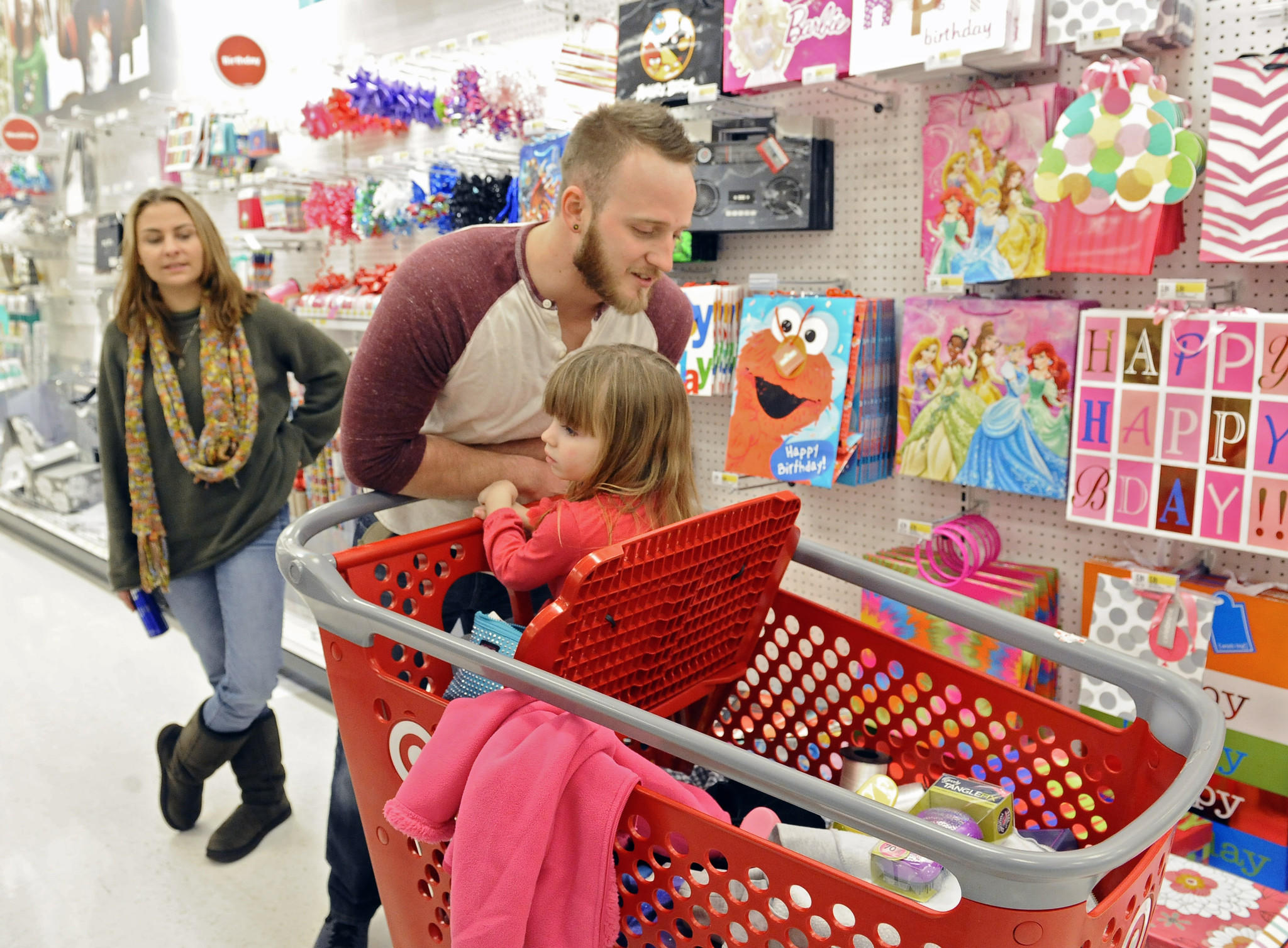 Rebecca Bauer, from left, and Chris Hobby, shop with their daughter Riley, 4, in the Target store at Canton Crossing for last minute Christmas gifts and wrapping paper.