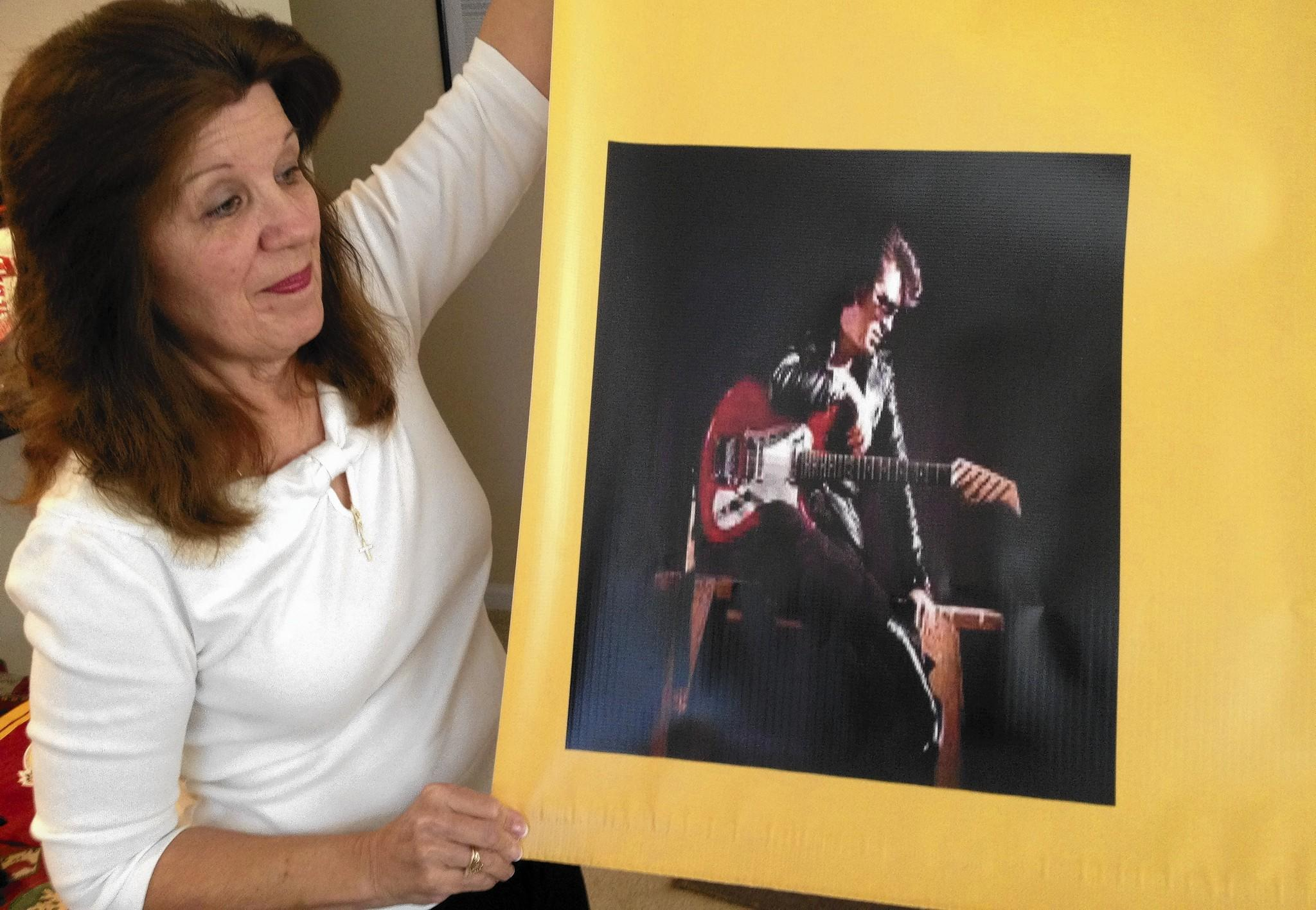 Beth Wray Webb holds the corner of a banner decorated with a photo of her father, guitarist Link Wray. The banner was made for the Portsmouth-based rock group Band of Tribes, which features Link Wray's grandson, Chris Webb.