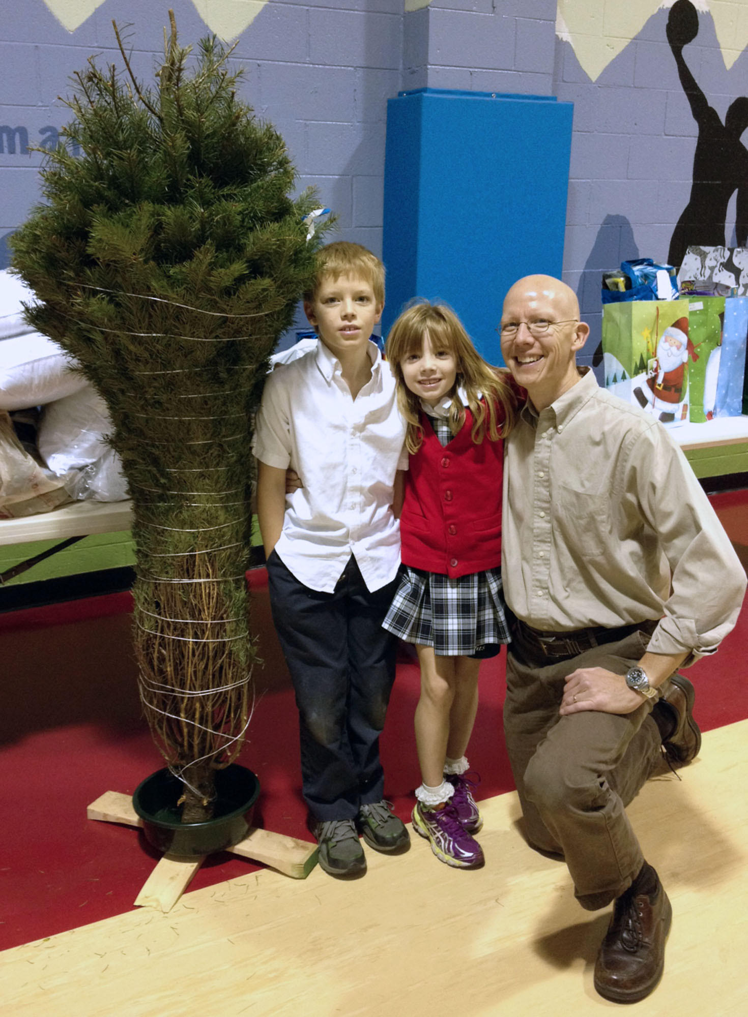 "David Beilfuss and his children deliver a Christmas tree and other donated gifts to the Salvation Army as part of the YMCA of the Foothills' Tribes program, which this year ""adopted"" 10 local families to help fill their needs this Christmas."