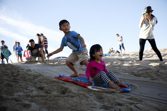 While their mom Jina takes pictures, Eden Inn, 2, of Redondo Beach lets out a scream, as brother Nathan, 5, rides their sled down a sand dune at the Hermosa Beach Pier on Christmas afternoon. The temperature reached the 80s in Hermosa Beach.