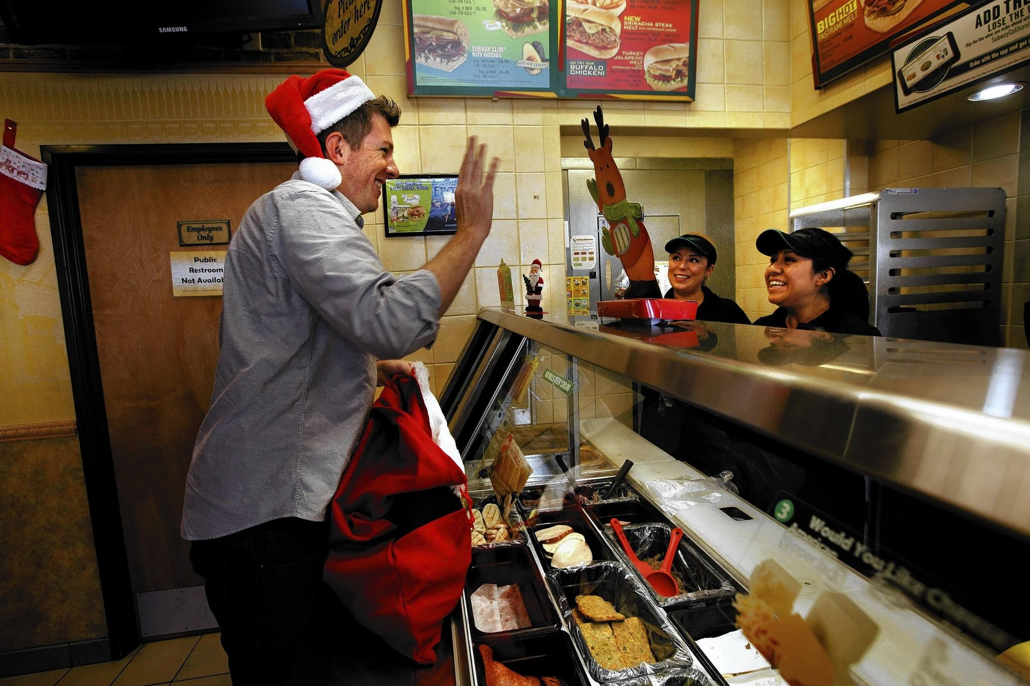 Michael Hope, 36, greets Subway employees Lisseth Pulidi, center, and Marie Mucino after brightening their day with cookies he and a friend handed out to those found working in West Hollywood on Christmas Day, as part of the Sacramento-based Cookie Project.