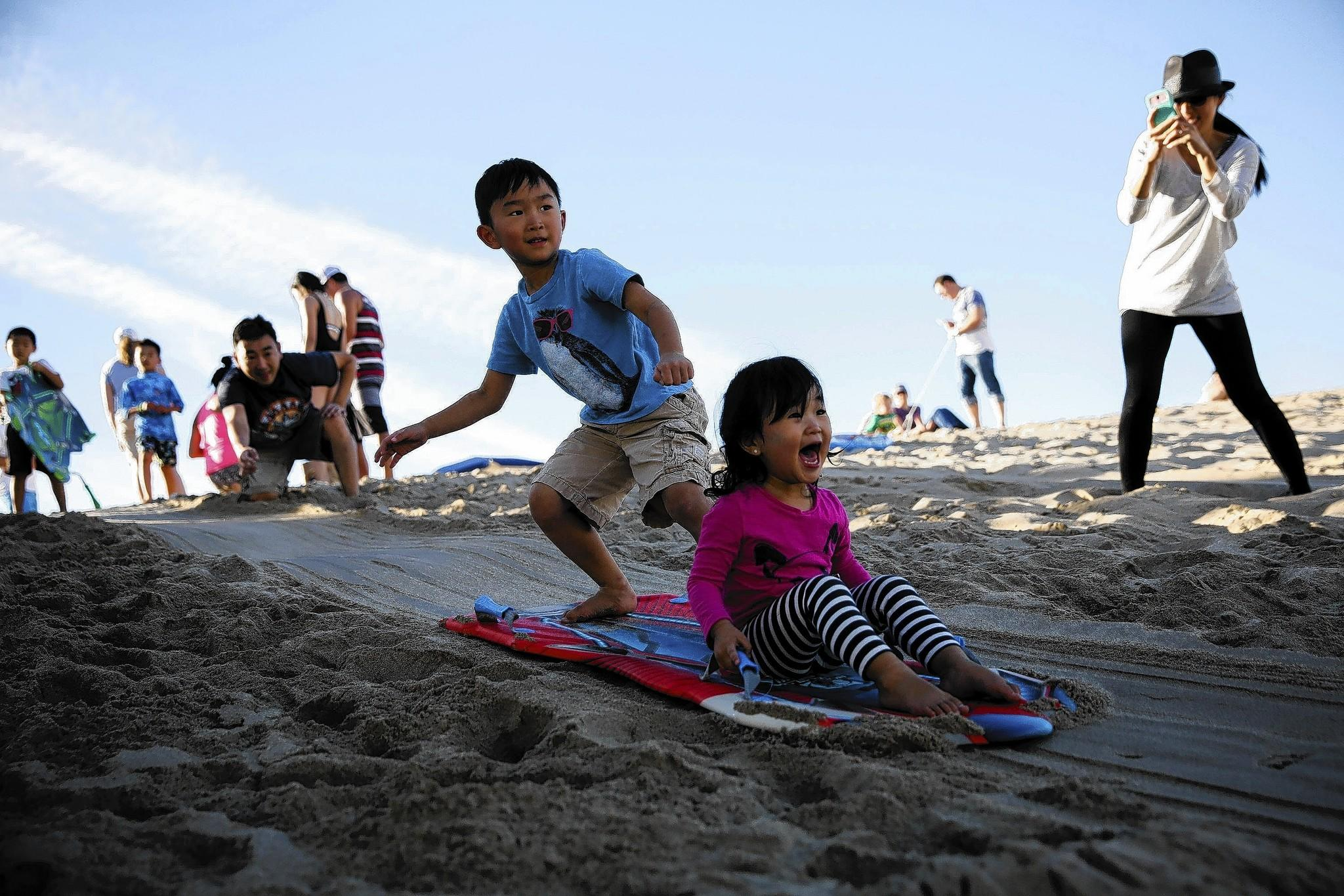 As their mother Jina takes pictures, Eden Inn, 2, from Redondo Beach, lets out a scream as brother Nathan,5, rides their sled down a sand dune at the Hermosa Beach Pier on Christmas afternoon.