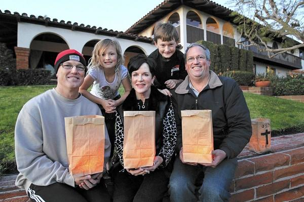 Siblings Lance Betson, Pam Barnett, Kevin Betson, foreground from left, and Lance's children Riley, 6, and Hayden, 8, background from left, pose for a photo at their former residence along Galaxy Drive in Newport Beach on Christmas Eve. The three siblings come together to light one last luminaria in honor of their mother, Joan Sue Betson, who passed away in January of this year.