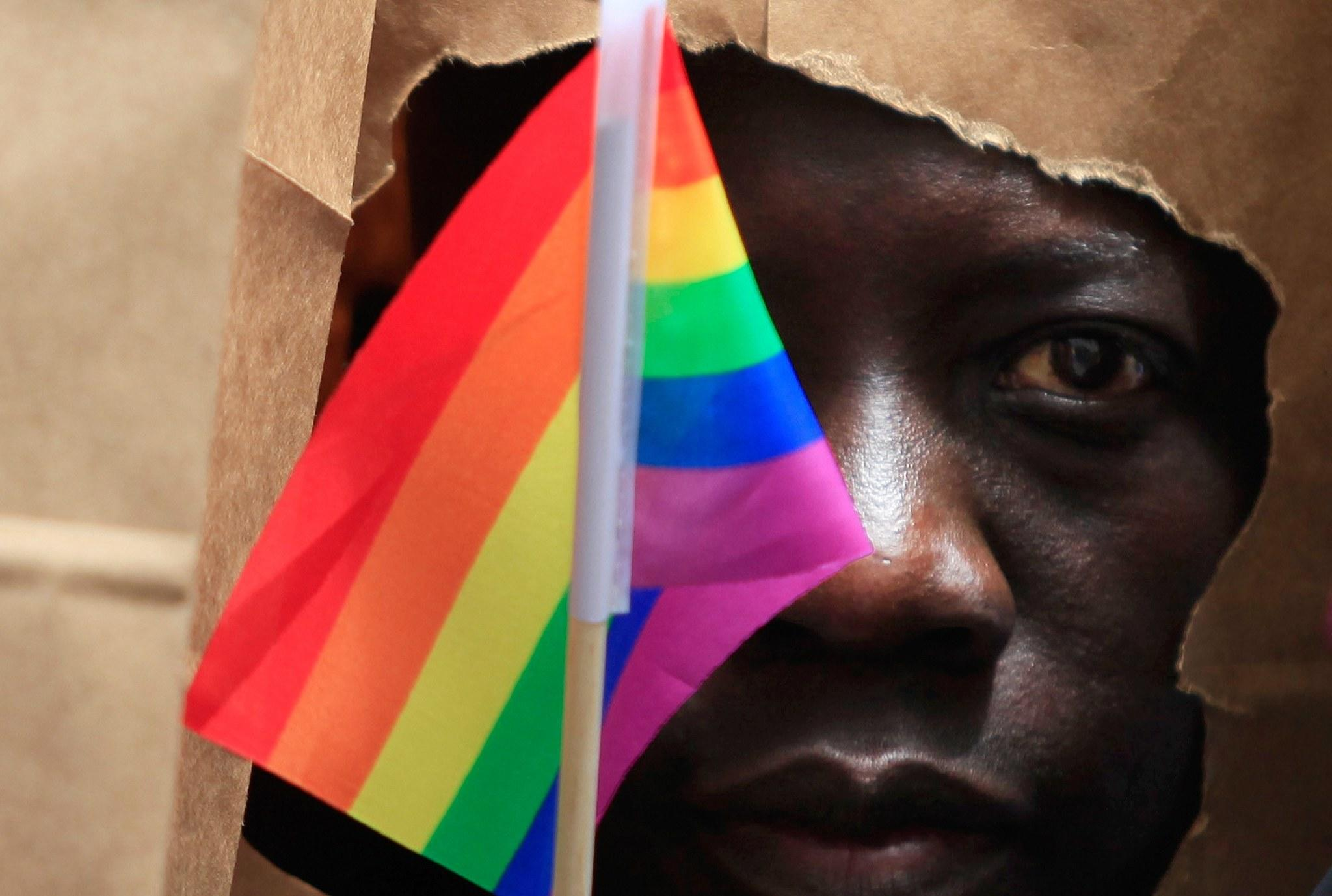 An asylum seeker from Uganda covers his face with a paper bag in order to protect his identity during the Pride Parade in Boston, June 8, 2013.