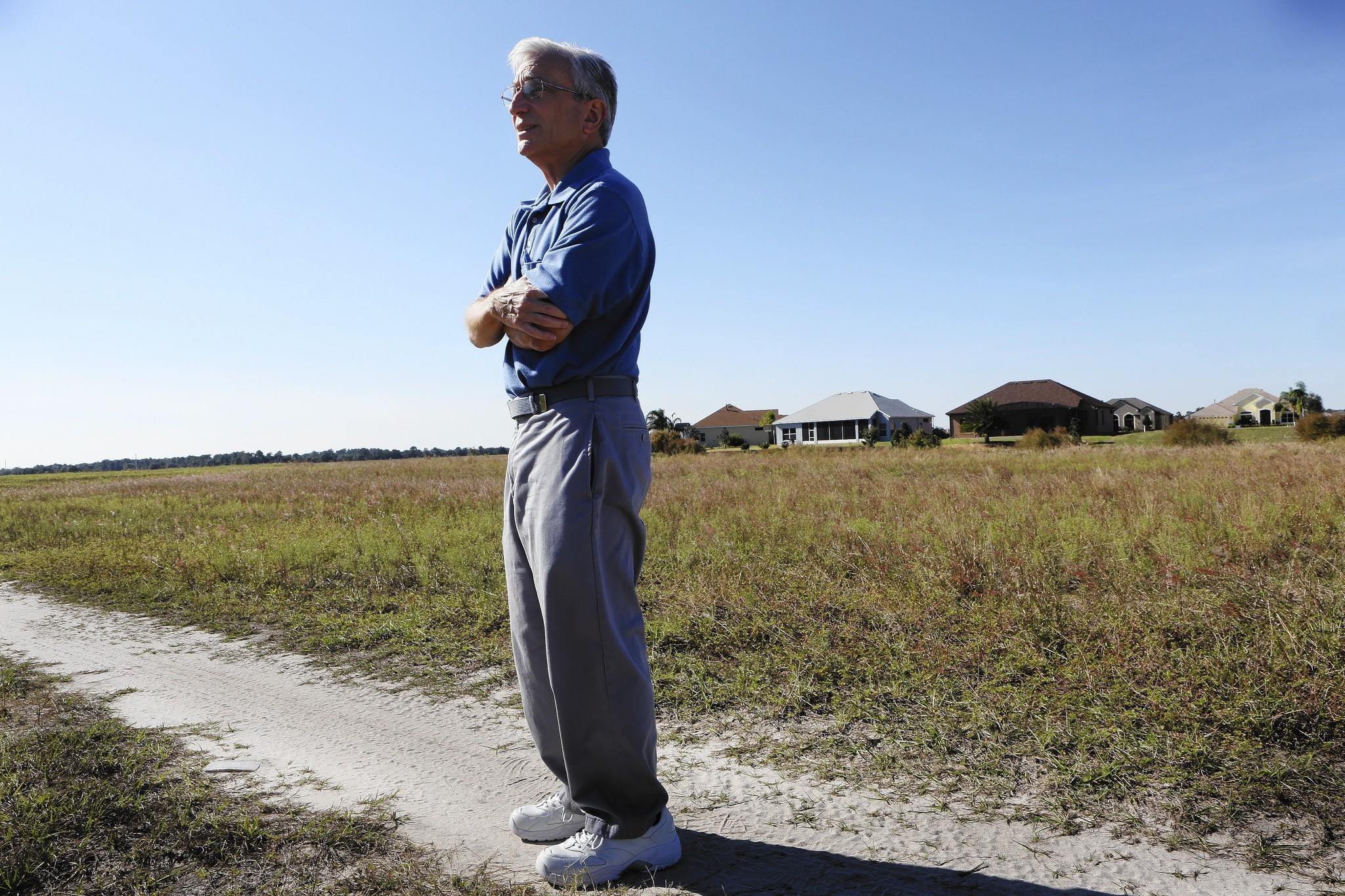 "Lakes of Mount Dora homeowners association vice president Fred Casiello, is pictured on a grass field on Thursday, December 12, 2013. Farming is illegal within the city limits, but developer Medallion Homes says its ""hay operation"" on pieces of an undeveloped 144-acre property helps fulfill a grass and dust control program required by the city."