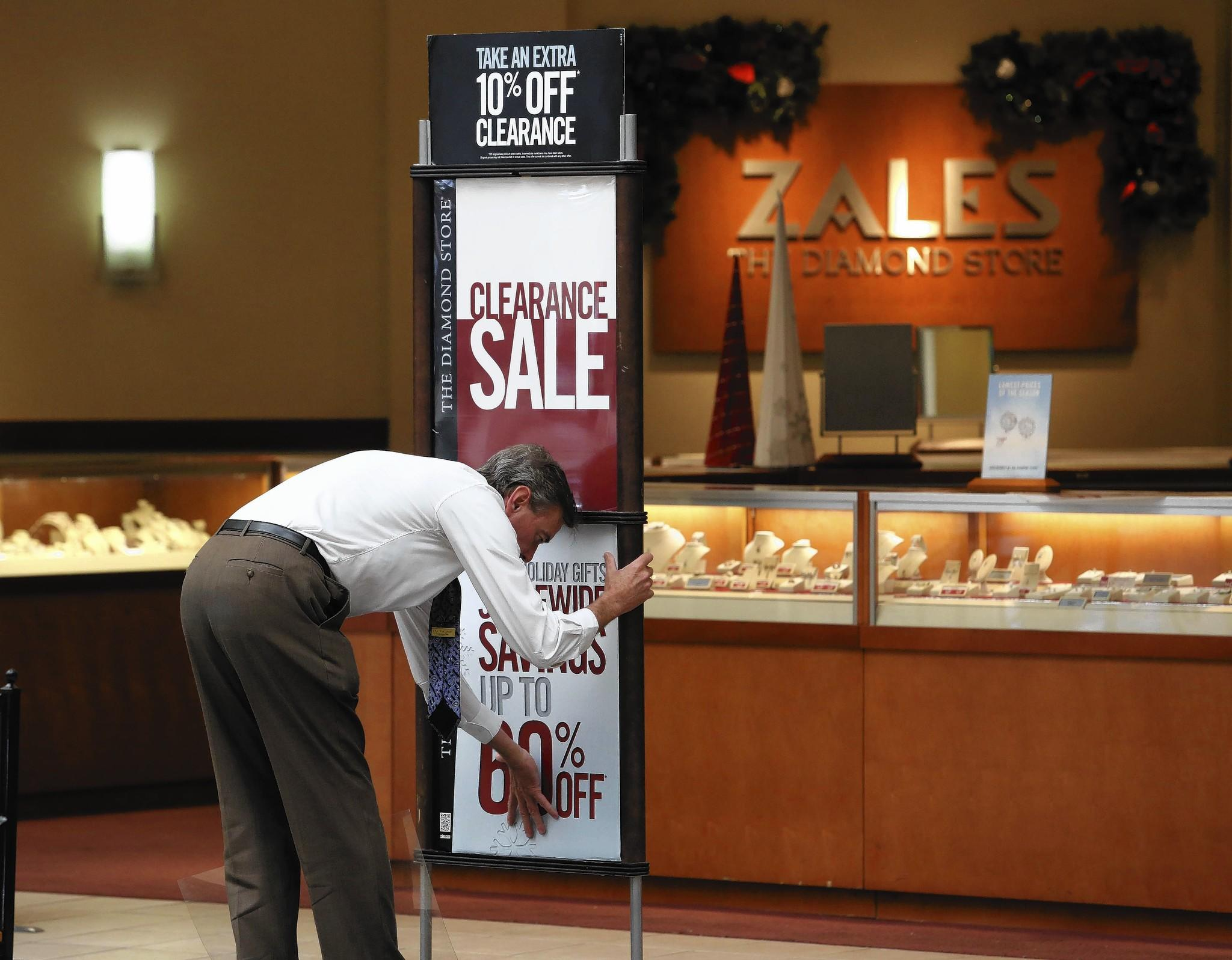 Shoppers at Fashion Square mall on East Colonial Drive the day after Christmas. A worker at Zales puts up the mark down signs.