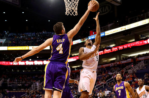 Laker forward Ryan Kelly tries to block a shot by Suns guard Ish Smith during a game Monday night in Phoenix.