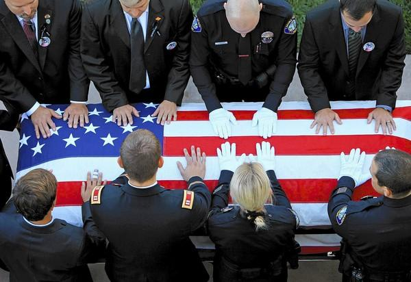 Pallbearers prepare to move Laguna Beach motorcycle Officer Jon Coutchie's casket into Mariners Church in Irvine in September.