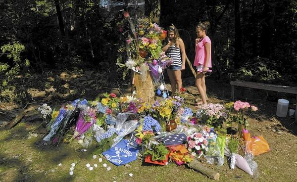 Recent Glastonbury High School graduates Allie Cichon, 18, (from left) and Ashley Strange, 18, pay their respects to Jane Modlesky on Wednesday afternoon at the memorial site where Modlesky was killed Sunday morning on Woodhaven Rd. in Glastonbury.