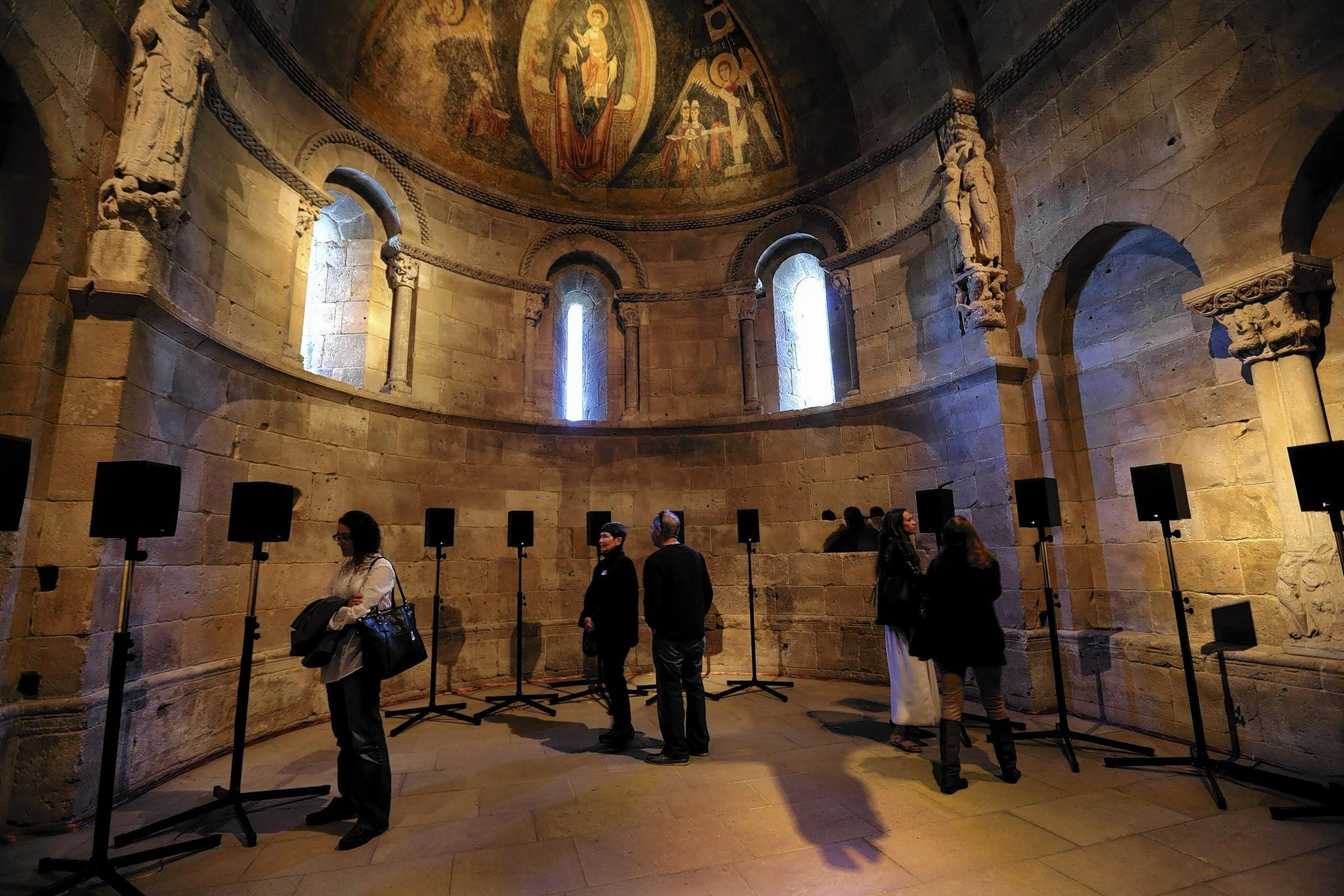 """Visitors listen to """"The Forty Part Motet (2001),"""" a sound installation by Janet Cardiff, in the Fuentiduena Chapel at the Cloisters Museum in New York on Sept. 23, 2013."""