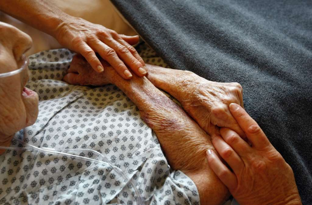 Hospice volunteers in Lakewood, Colo. caress the hands of terminally ill patient. While only 30% of American patients have advance directives on file, a new survey found that 79% of the patients who responded would like to talk to their doctors about end-of-life care.