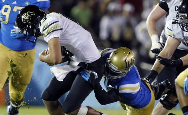 UCLA linebacker Isaako Savaiinaea, right, tackles Colorado quarterback Sefo Liufau during a game in November. Savaiinaea will see plenty of playing time Tuesday against Virginia Tech in the Sun Bowl.