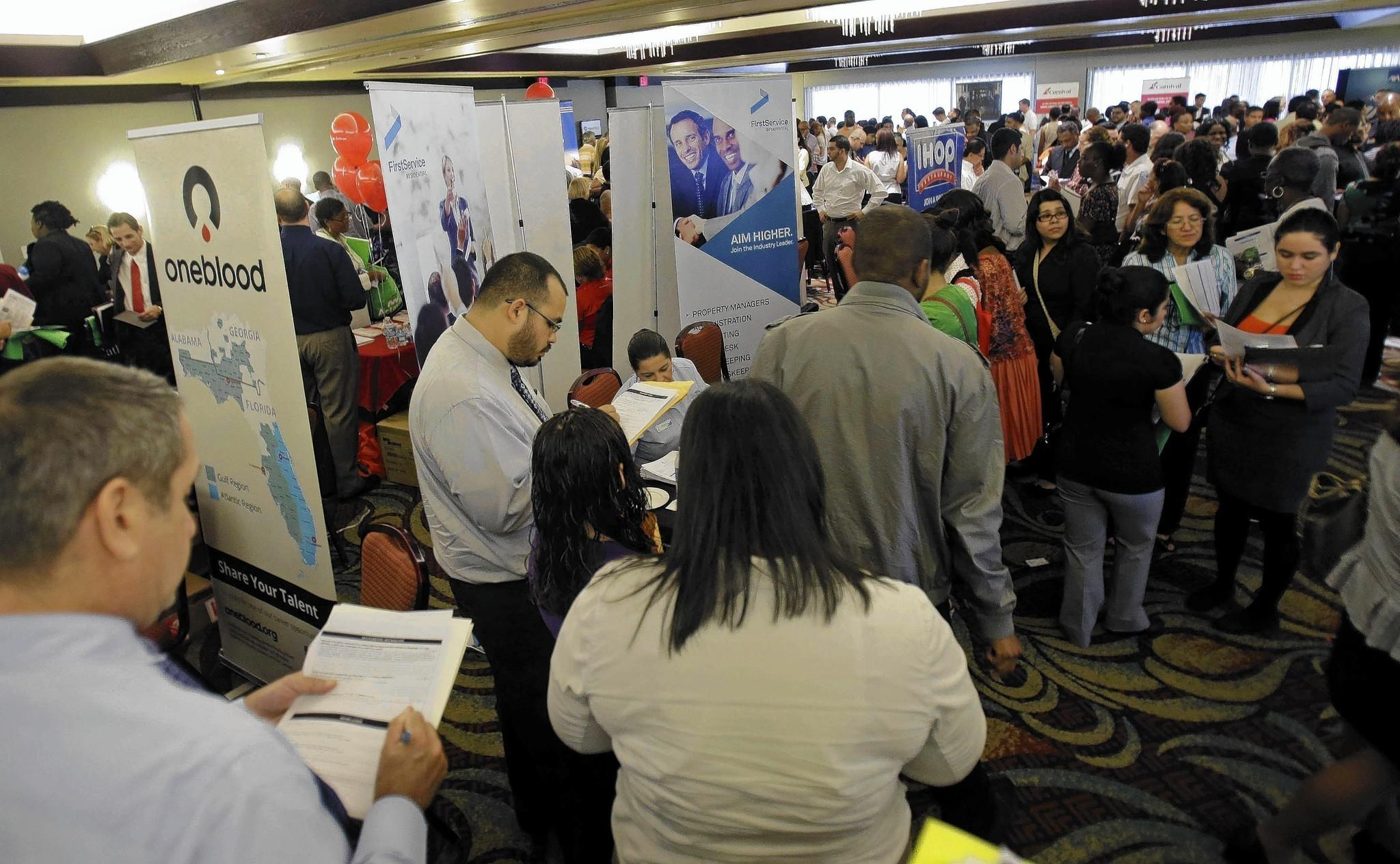 People look for opportunities at a job fair in Miami Lakes, Fla., last summer.