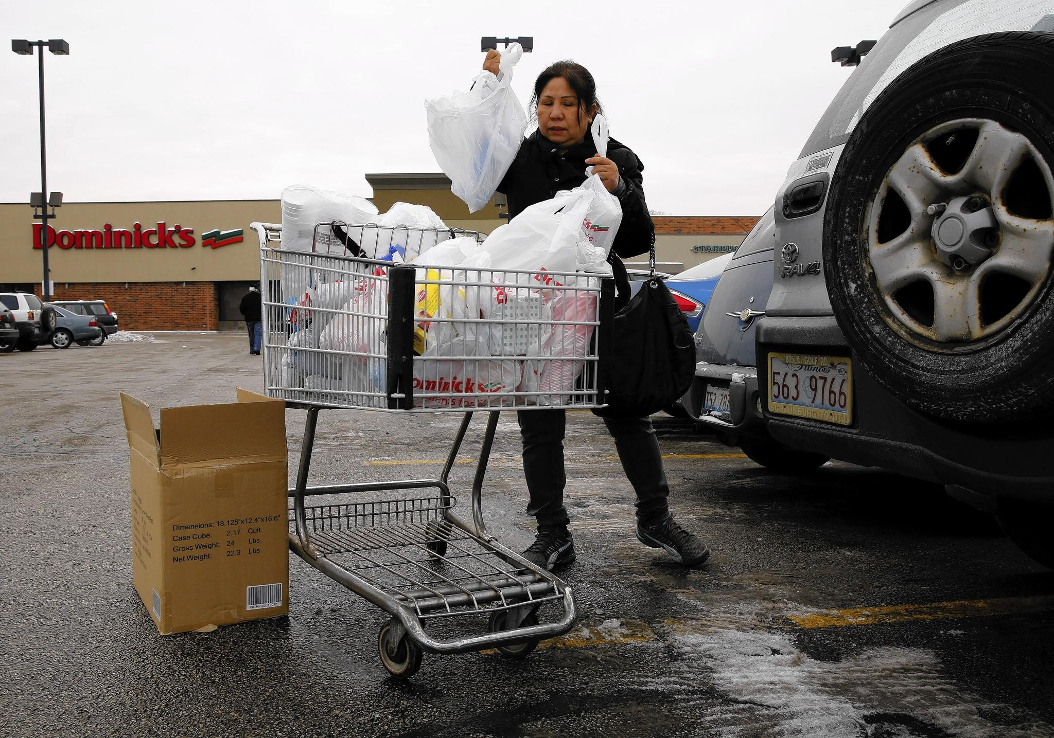 Long Nguyen, 50, of Chicago, loads up her car Dec. 16 after shopping for discounted groceries at a Dominick's store that is closing at Damen and Ridge avenues on the city's North Side.