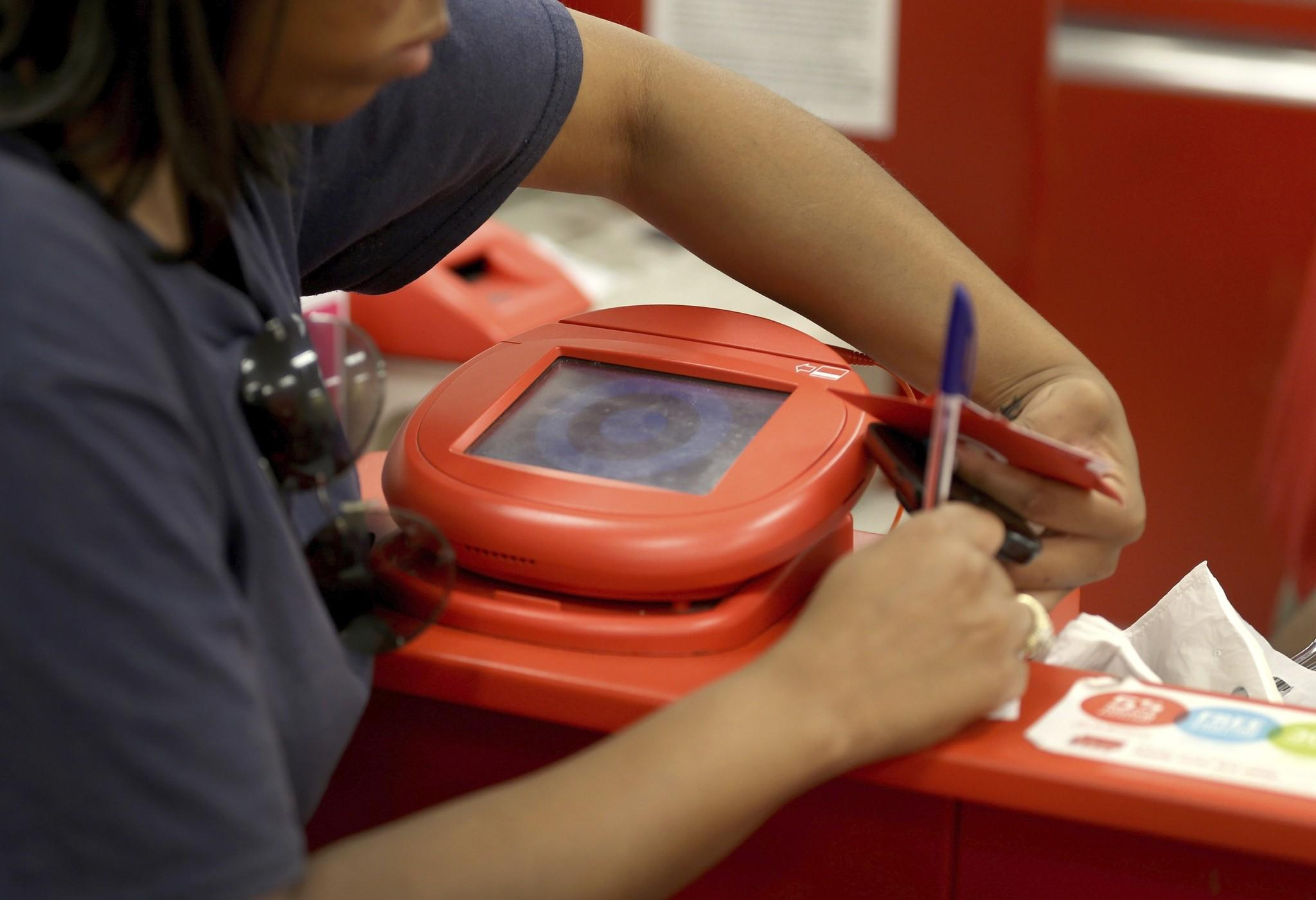 A customer signs a credit card statement next to a scanner in a Target store on December 19, 2013 in Miami, Florida. Target announced that about 40 million credit and debit card accounts of customers who made purchases by swiping their cards at terminals in its U.S. stores between November 27 and December 15 may have been stolen.