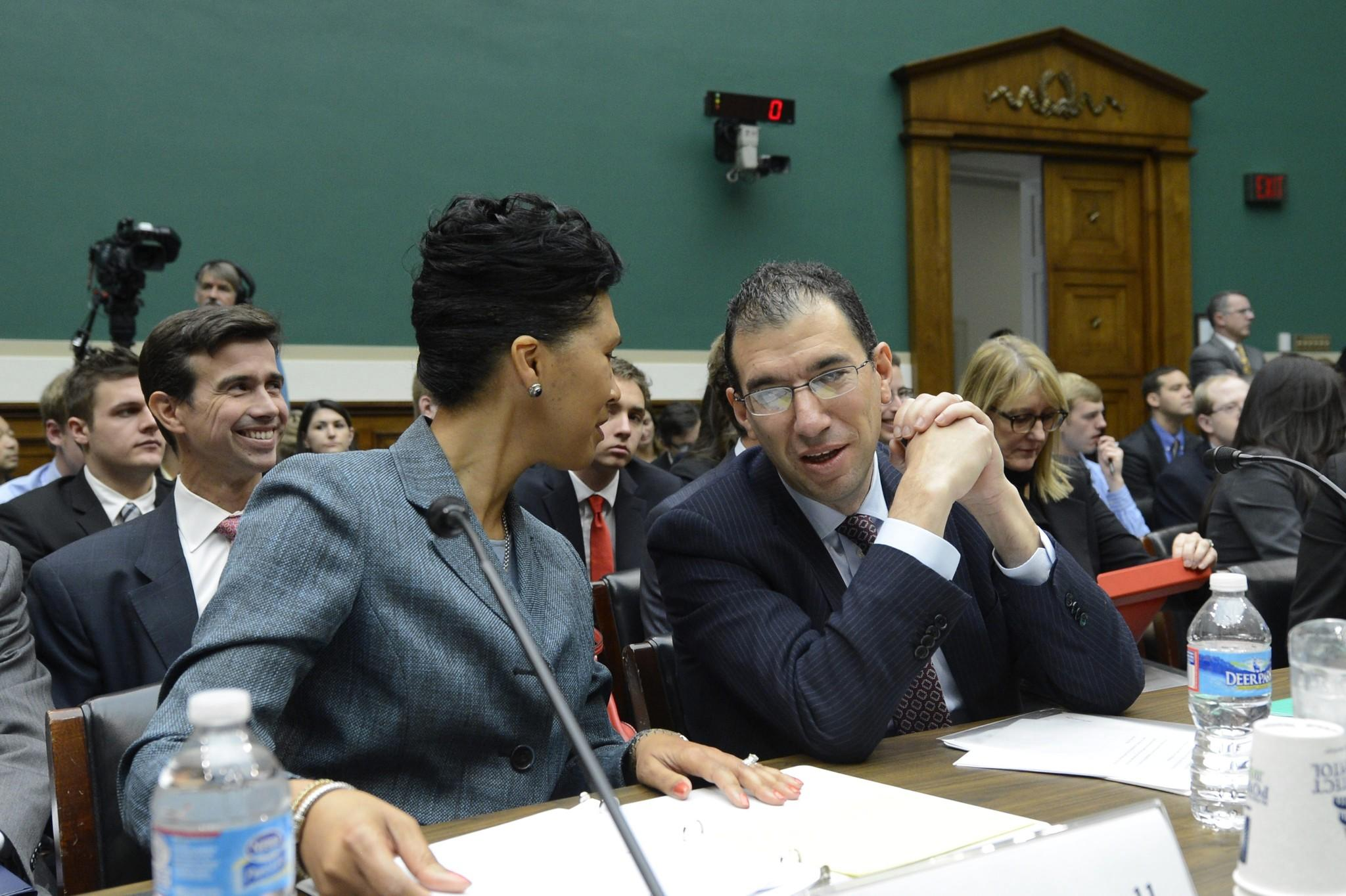 Senior Vice President of CGI Federal Cheryl Campbell (left) and group executive Vice President for Optum/QSSI Andrew Slavitt speak with one another before appearing before a US House Energy and Commerce Committee hearing.