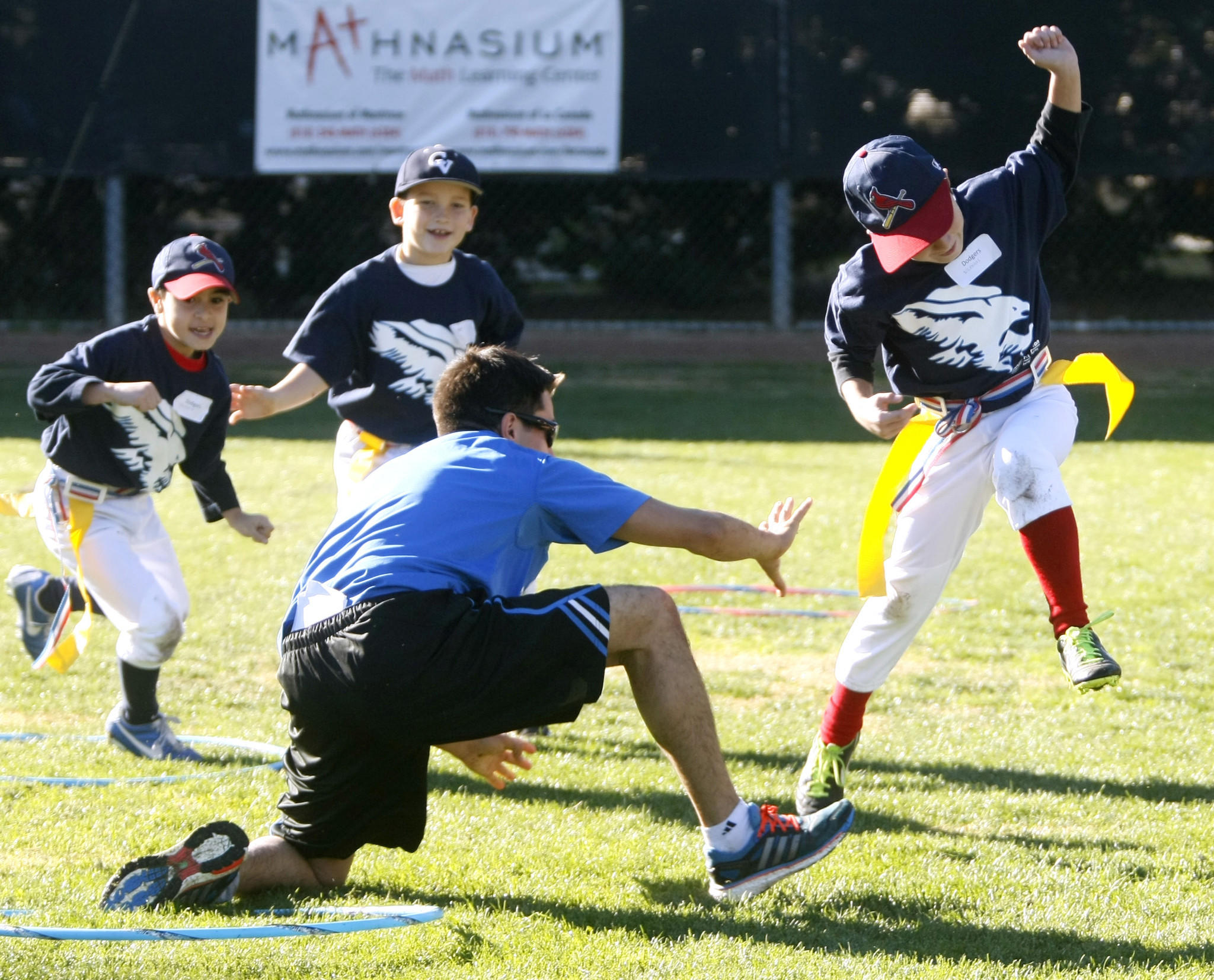 Nicholas Boghossian, 9, right, tries to avoid a coach's grab in flag tag at the annual Falcon Winter Baseball Camp at Stengel Field in Glendale on Thursday, Dec. 26, 2013. Crescenta Valley High School baseball coach Phil Torres runs the camp.