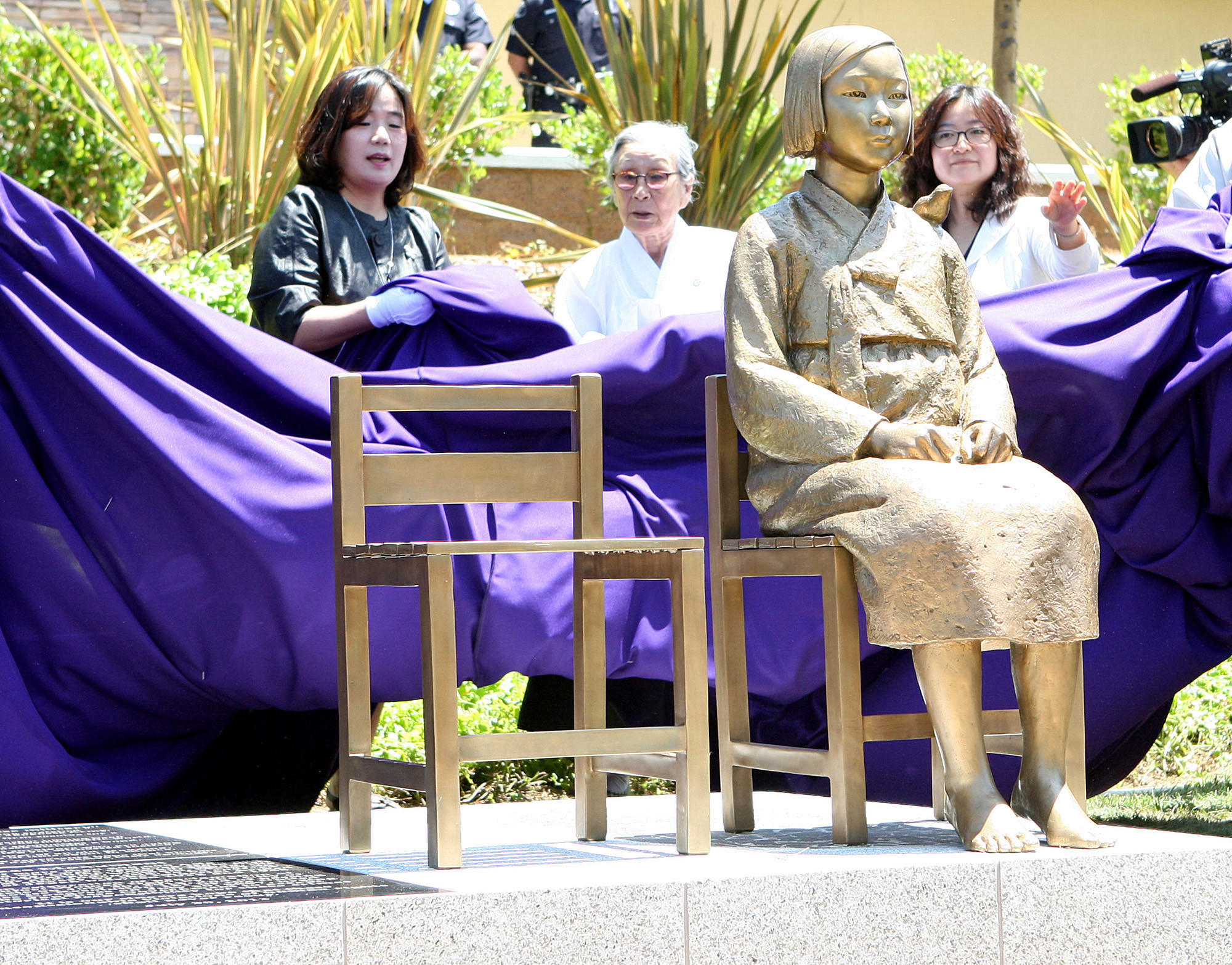 Bok-dong Kim, a comfort woman survivor, is directly behind the monument as it is being unveiled at the unveiling ceremony of the Comfort Women Memorial Monument in Glendale on Tuesday, July 30, 2013.